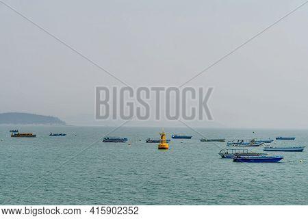Small Fishing Boats Anchored In Harbor Near Yellow Buoy On Hazy Overcast Morning.