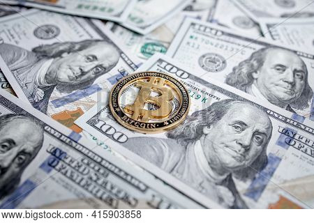 Golden Symbolic Coin Bitcoin On Banknotes Of One Hundred Dollars. Exchange Bitcoin Cash For A Dollar