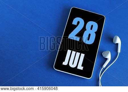 July 28. 28 St Day Of The Month, Calendar Date. Smartphone And White Headphones On A Blue Background