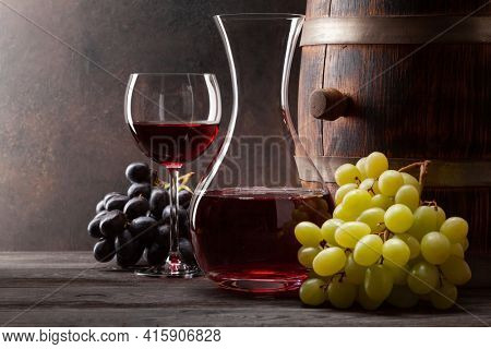 Wine decanter, glass of red wine and old wooden barrel. With copy space