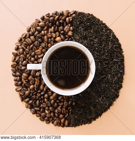 Beige Flat Lay Background With White Ceramic Coffee Cup, Roasted Coffee Beans And Dried Tea Leaves.