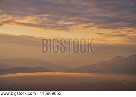 Scenic Dawn Mountain Landscape With Golden Low Clouds In Valley Among Mountains Silhouettes Under Cl