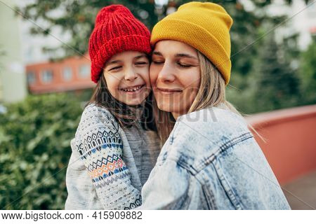 Portrait Of The Happy Little Girl In Red Hat Hugging Her Mom In Yellow Hat, Denim Jacket. Cute Kid E