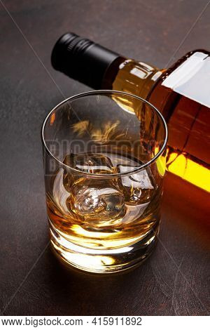 Scotch whiskey bottle and glass on stone table