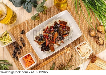 Flat Lay Of Mix Vegetable, Shiitake And Bamboo Shoots In Brown Sauce Served With Rice