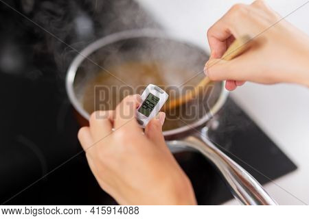 Close-up Of Woman Measuring Temperature Of Food, Electronic Thermometer. Hands Of The Cook, Pastry C
