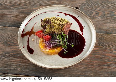 Top View Of Beef Meat With Pistachio Topping Served With Cranberry Sauce. Tasty Meal With Fruits, Be