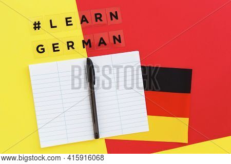 Red And Yellow Background, Inscription With Hashtag Learn German, Notebook And Pen, Flag Of Germany,