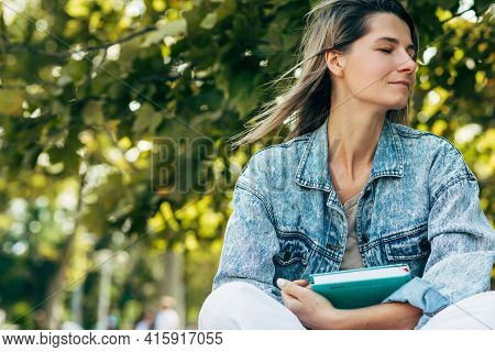 A Beautiful Female With Closed Eyes With A Book In Hand While Sitting On The Bench On A Sunny Day In