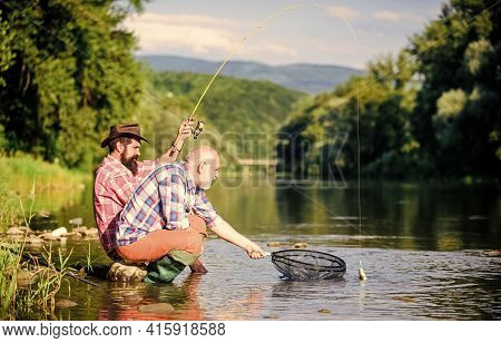 Autumn Fishing Spinning. Two Male Friends Fishing Together. Retired Dad And Mature Bearded Son. Happ