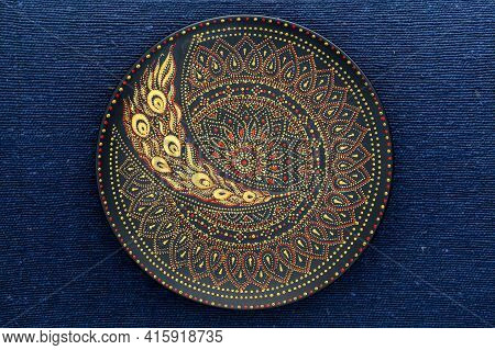 Decorative Ceramic Plate With Black, Red And Golden Colors, Painted Plate On The Background Of Blue