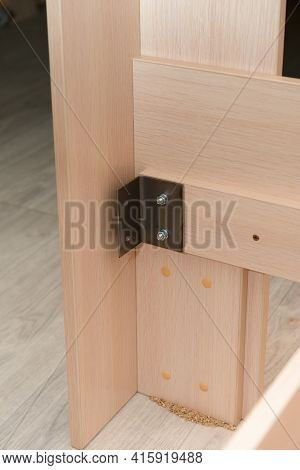 Assembling Furniture With A Metal Corner. Chipboard Panels Are Assembled Together.