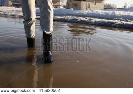Gray Pants, Rubber Boots, Early Spring, Deep Mud Puddle, Feet Stand In A Deep Mud Puddle In Spring.
