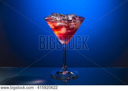A Glass Of Red Martini With Ice On A Blue Background. Photo Of Food.