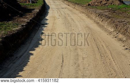 A New Path Through The Fields. An Excavator And A Grader Drove The Way Through A Spade And Rolled Th