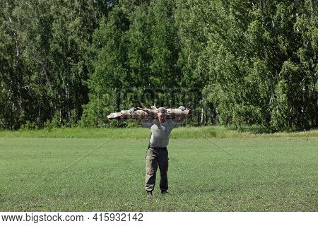 Strong Man In Hiking Clothes Is Walking Through Green Field And Carrying Large Heavy Log From Forest