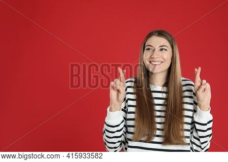 Woman With Crossed Fingers On Red Background, Space For Text. Superstition Concept
