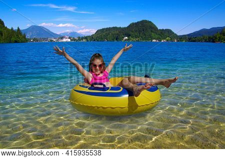Girl on inflatable ring in the lake . Child on rubber yellow circle resting in nature. Bled. Slovenia, Europe.