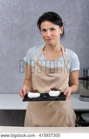 Pastry Chef Holding Black Tray With Cake Anna Pavlova. Meringue Cake With Fresh Berries.