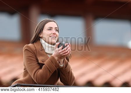 Happy Tenant Drinking Coffee Looking Away In A Balcony In Winter