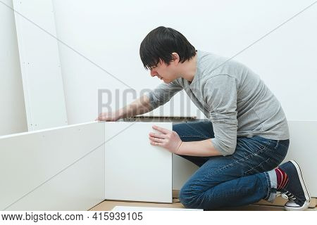 Man Assembling New Furniture At Home. Furniture Assembly Yourself. Young Worker Collects A Bookshelf