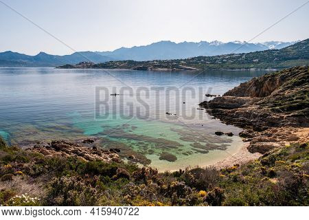 A Lone Kayaker Paddles Across A Small Shallow Cove On The Translucent Mediterranean Sea On The Coast