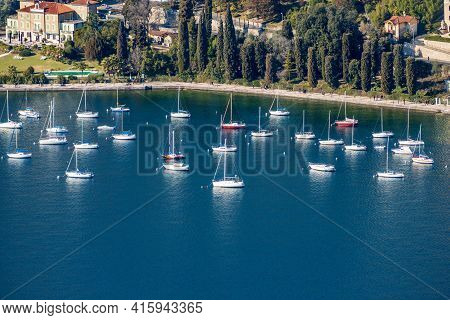 Aerial View Of Sailboats Moored In The Port Of Garda Town, Tourist Resort On The Coast Of Lake Garda