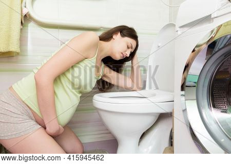 Sick Young Woman With Pain In Stomach Is Vomiting In Toilet Sitting On The Floor At Home. Young Woma