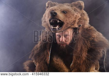 Low Key Portrait Of A Bearded War Shaman In Bearskin With An Ancient Ax In His Hands. High Quality C