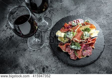 Antipasto Background. Different Italian Snacks With Red Wine On Dark Background. Traditional Spanish