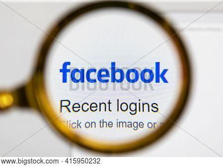 Moscow, Russia - 29 March 2021: View The Facebook Homepage Through A Golden Magnifier, Company Logo.