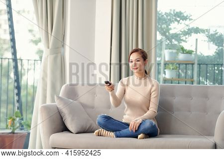 Women Watching Tv On The Sofa At Home With Remote Control