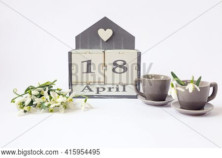 Calendar For April 18: Cubes With The Number 18, The Name Of The Month In English, Two Gray Coffee C