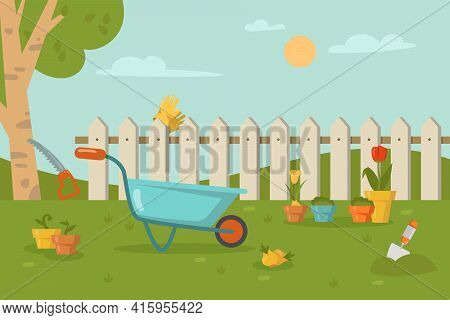 Garden Tools Lying On Grass In Front Of Fence. Wheelbarrow, Shovel, Sawing A Tree, Gloves On Fence,
