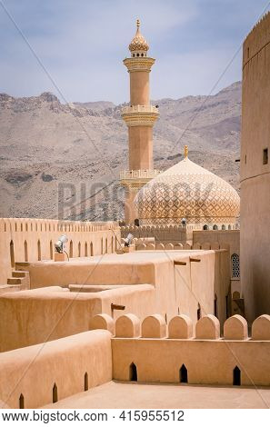 Nizwa, Oman - 04.06.2018: Minaret, Dome And Walls Of Medievel Arabian Fort Of Nizwa, Oman. Hot Day I