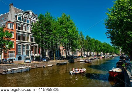 Amsterdam canal with tourist boat and old houses