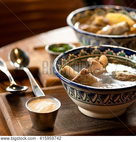 Bowls With Rich Hearty Meat Soup With Broth And Pork Ribs On Wooden Table. Nutritious Wholesome Food