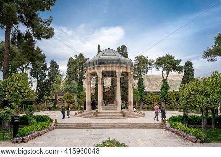 Shiraz, Iran - 04.14.2019: People Walking In Persian Garden With A Stone Gazebo. Tomb Of Hafez Shira