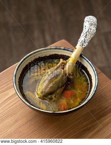 Bowl Of Broth With Meat On Bone. Portion Of Rich Soup With Boiled Poultry Leg And Vegetables On Wood