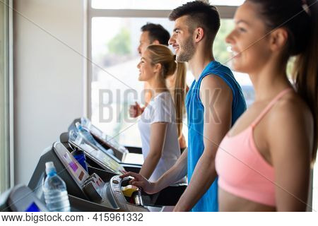 Group Of Happy Fit Young People Running On A Treadmill In Health Club
