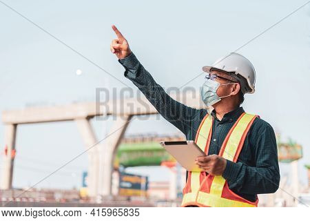 Male Engineer Points To An Elevated Expressway Construction Project