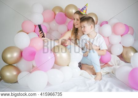 Photo Of Joyful Woman With Kid Boy Smiling And Taking Selfie Photo On Cellphone  With Balloon. Birth