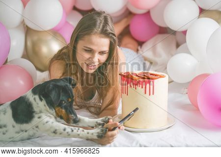 Lovely Lady In Pajama Making Selfie In Her Bedroom Using Phone With Her Dog. Indoor Portrait  Girl W