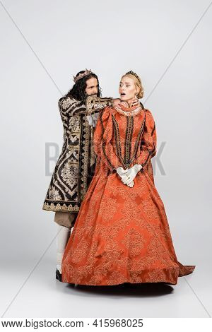 Full Length Of Hispanic King In Medieval Clothing Choking Shocked Queen In Crown On White.