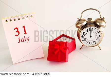 Calendar Date On Light Background With Red Gift Box With Ring And Alarm Clock With Copy Space. July