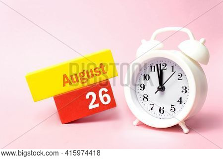 August 26th. Day 26 Of Month, Calendar Date. White Alarm Clock On Pastel Pink Background. Summer Mon