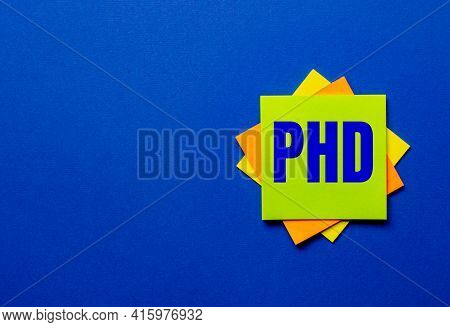 The Word Phd Is Written On Bright Stickers On A Blue Background