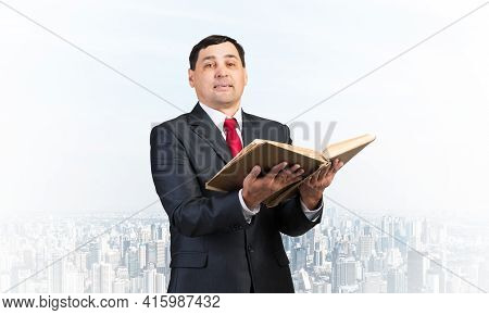 Serious Businessman Holding Open Old Book. Adult Man In Business Suit Standing On Cloudy Cityscape B