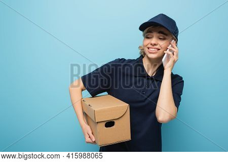 Discouraged Courier Calling On Smartphone While Holding Parcel Isolated On Blue.
