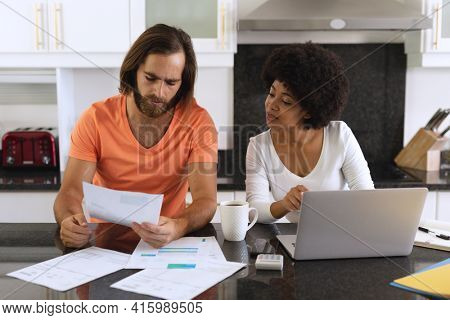 Diverse couple sitting in kitchen using laptop and paying bills. staying at home in isolation during quarantine lockdown.